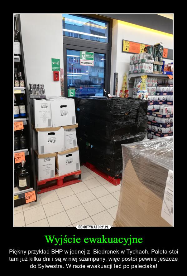 Wyjście ewakuacyjne – Piękny przykład BHP w jednej z  Biedronek w Tychach. Paleta stoi tam już kilka dni i są w niej szampany, więc postoi pewnie jeszcze do Sylwestra. W razie ewakuacji leć po paleciaka!